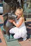 Menina que senta-se em um abraço com um cão de bronze Foto de Stock Royalty Free