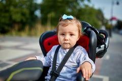 A menina que senta-se em um assento da bicicleta do bebê de uma bicicleta de sua ansiedade das emoções da segurança do pai caçoa  Imagens de Stock Royalty Free