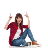 Menina que senta-se em um assoalho que cola para fora a língua e que aponta acima Foto de Stock Royalty Free