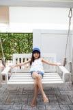 Menina que senta-se em um balanço Foto de Stock
