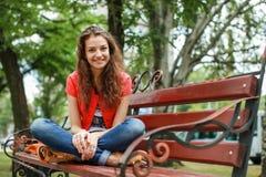 Menina que senta-se em um banco Fotos de Stock