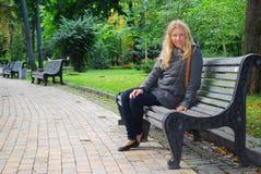 Menina que senta-se em um banco. Imagens de Stock