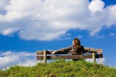 Menina que senta-se em um banco imagem de stock royalty free