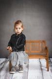 Menina que senta-se em um banco de madeira Fotografia de Stock