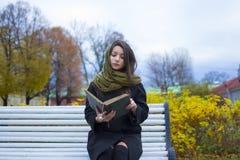 Menina que senta-se em um banco e que lê um livro Imagem de Stock Royalty Free