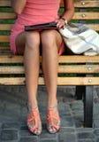 Menina que senta-se em um banco e que lê um livro Imagens de Stock Royalty Free