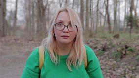 A menina que senta-se em um banco no parque e olha para baixo e olha então acima na câmera filme
