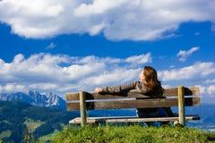Menina que senta-se em um banco sobre o céu azul Fotografia de Stock