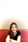 Menina que senta-se em um banco vermelho Fotos de Stock