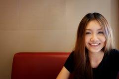 Menina que senta-se em um banco vermelho Fotografia de Stock Royalty Free