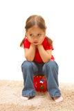 Menina que senta-se em um brinquedo plástico vermelho Fotografia de Stock Royalty Free