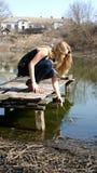 Menina que senta-se em um cais Fotos de Stock