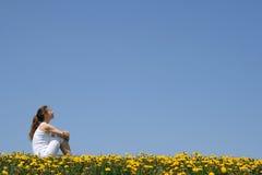 Menina que senta-se em um campo Fotos de Stock