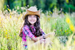 Menina que senta-se em um campo que veste um chapéu de vaqueiro Fotografia de Stock