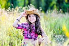 Menina que senta-se em um campo que veste um chapéu de vaqueiro Imagens de Stock Royalty Free