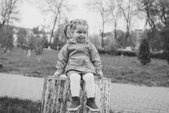 Menina que senta-se em um coto Foto de Stock