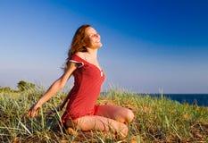 Menina que senta-se em um dune-3 Foto de Stock