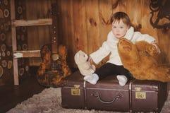 Menina que senta-se em um fundo marrom de madeira da mala de viagem velha grande Foto de Stock