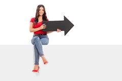 Menina que senta-se em um painel e que guarda uma seta Fotografia de Stock