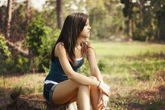 Menina que senta-se em um parque Fotos de Stock Royalty Free