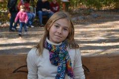Menina que senta-se em um parque Imagem de Stock