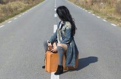 Menina que senta-se em um saco na estrada Fotos de Stock Royalty Free
