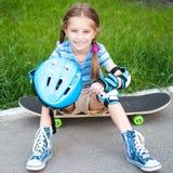 Menina que senta-se em um skate imagem de stock royalty free