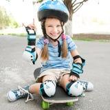 Menina que senta-se em um skate imagens de stock royalty free