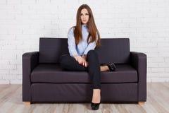 Menina que senta-se em um sofá preto fotografia de stock
