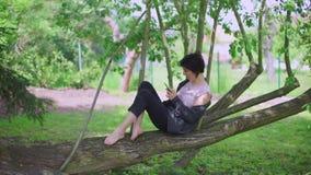 A menina que senta-se em uma árvore usa o telefone vídeos de arquivo