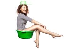 A menina que senta-se em uma bacia monta. Fotos de Stock