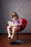 Menina que senta-se em uma cadeira com um portátil fotografia de stock