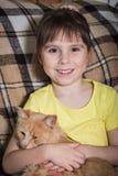 Menina que senta-se em uma cadeira e que abraça o gato vermelho Fotos de Stock Royalty Free