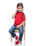 Menina que senta-se em uma cadeira e que fala pelo smartphone Fotografia de Stock