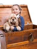 Menina que senta-se em uma caixa com um cão Imagens de Stock Royalty Free