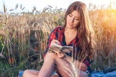 Menina que senta-se em uma camisa do campo, trigo que relaxa na natureza, cabelo moreno bonito Escreve pnans para o futuro na Imagem de Stock