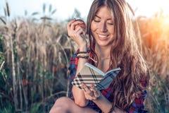 Menina que senta-se em uma camisa do campo, trigo que relaxa na natureza, cabelo moreno bonito Guarda uma maçã, bloco de notas pn Fotografia de Stock Royalty Free