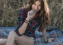 Menina que senta-se em uma camisa do campo, trigo que relaxa na natureza, cabelo moreno bonito Mantém o bloco de notas pnany para Imagem de Stock Royalty Free
