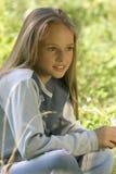 A menina que senta-se em uma grama no parque Fotografia de Stock