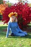 Menina que senta-se em uma grinalda das folhas Imagens de Stock