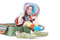 A menina que senta-se em uma mala de viagem Foto de Stock