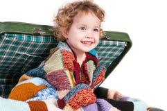 A menina que senta-se em uma mala de viagem Imagem de Stock