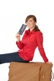 Menina que senta-se em uma mala de viagem fotos de stock