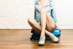 Menina que senta-se em uma mala de viagem Imagem de Stock