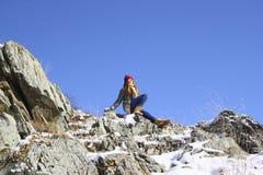 A menina que senta-se em uma rocha e medita Imagem de Stock