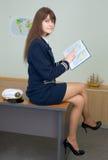 Menina que senta-se em uma tabela com o atlas Foto de Stock