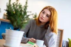 Menina que senta-se em uma tabela com uma xícara de café Fotografia de Stock