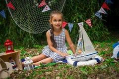 Menina que senta-se entre a decoração marinha Imagens de Stock Royalty Free
