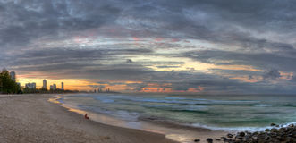 Menina que senta-se longitudinalmente na praia no por do sol foto de stock royalty free