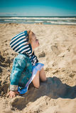 Menina que senta-se na areia na praia Fotografia de Stock Royalty Free
